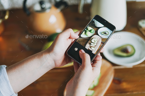Woman take smartphone photo of still life of fresh avocado on wooden table - Stock Photo - Images
