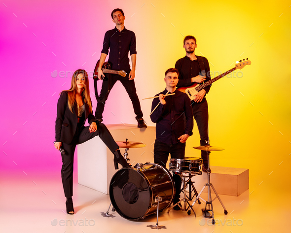 Young caucasian musicians, band performing in neon light on gradient studio background - Stock Photo - Images