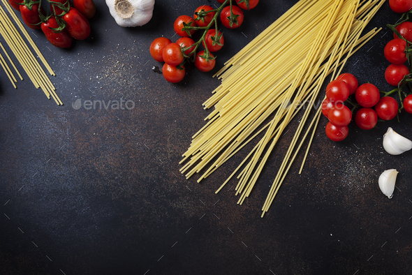 spaghetti, tomato and garlic on the black table - Stock Photo - Images