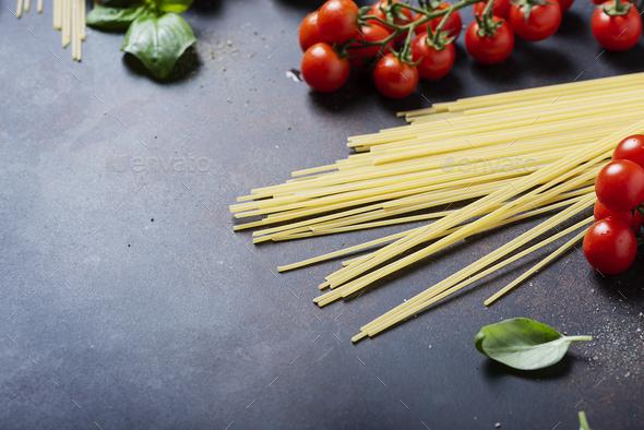 spaghetti, tomato, basil and garlic on the black table - Stock Photo - Images