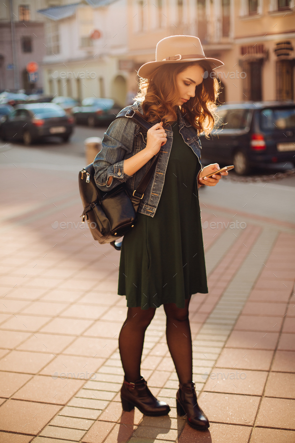 Stylish woman in hat, walking after shopping and using smar tphone - Stock Photo - Images