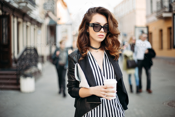 Fashionable brunette in striped suite and sunglasses walking at street - Stock Photo - Images