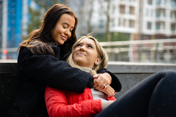 Smiling Best Friends Embracing And Sitting On The Ground In City - Stock Photo - Images