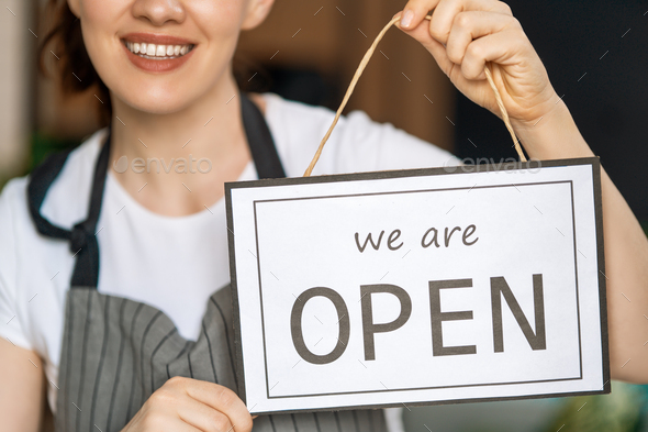 business owner holding the sign for the reopening - Stock Photo - Images
