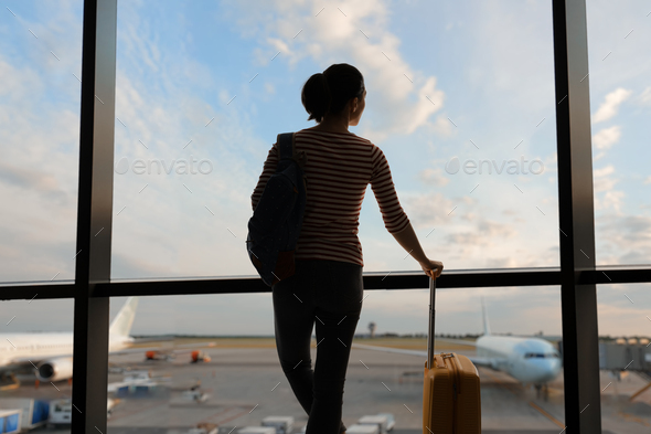 woman looking at a plane at the airport - Stock Photo - Images