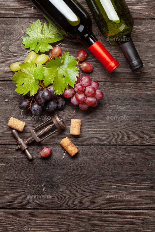 Various grapes, wine bottles and corkscrew - Stock Photo - Images