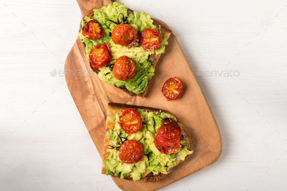Avocado and roasted tomatoes toasts - Stock Photo - Images