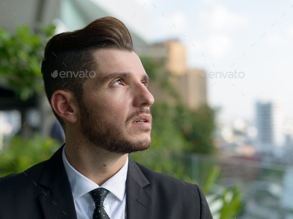 Handsome bearded Hispanic businessman with nature in the city outdoors - Stock Photo - Images