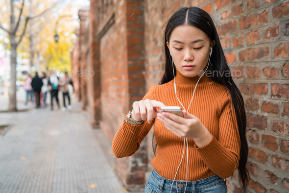 Asian woman using her mobile phone. - Stock Photo - Images