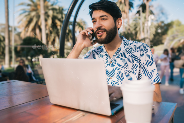 Man using his laptop and talking on the phone. - Stock Photo - Images