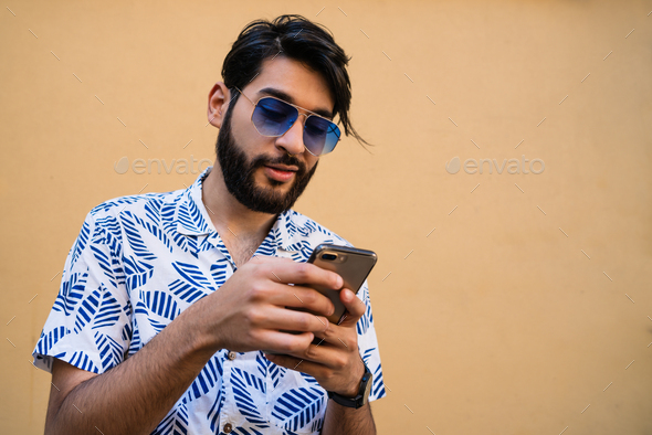 Young latin man using his mobile phone. - Stock Photo - Images