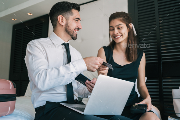 Two business people buying flight tickets with credit card. - Stock Photo - Images