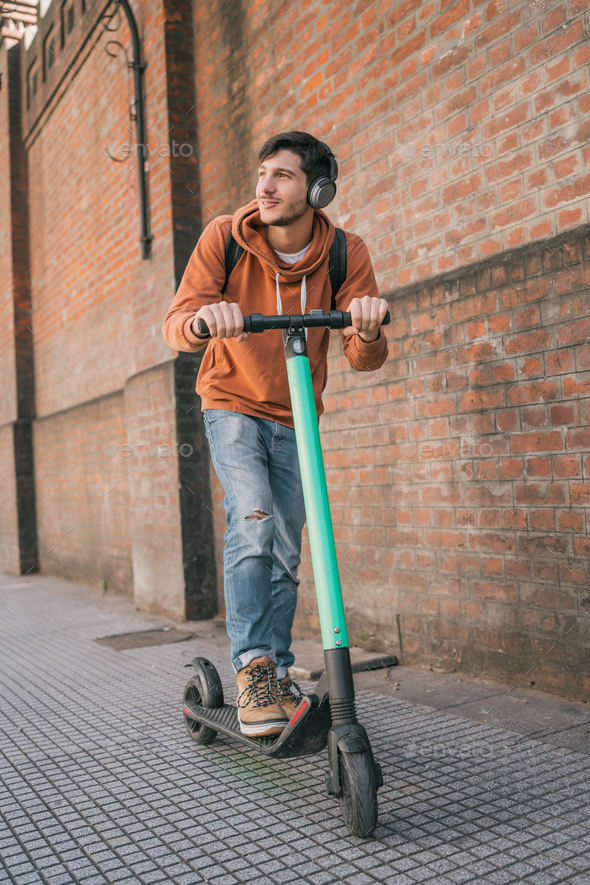 Young man driving electric scooter. - Stock Photo - Images