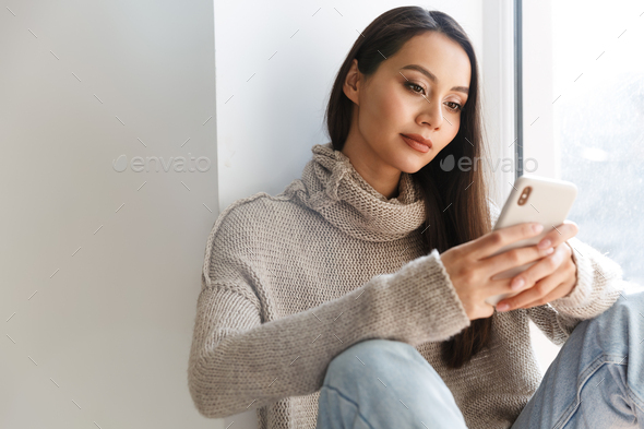 Image of asian woman typing on mobile phone while sitting on window sill - Stock Photo - Images
