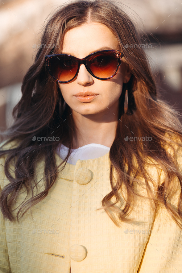 Brunette woman in sunglasses and yellow coat - Stock Photo - Images