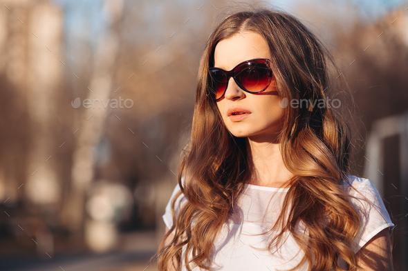 Beautiful seductive woman in sunglasses walking at street - Stock Photo - Images