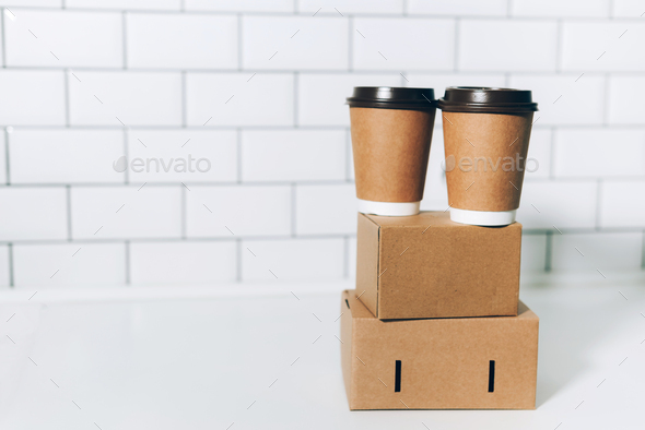 Craft paper cups with coffee to go and food box, lunch on tabletop over white kitchen. Banner, copy - Stock Photo - Images