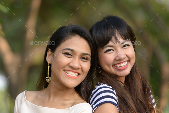 Portrait of two young Asian women together at the park - Stock Photo - Images