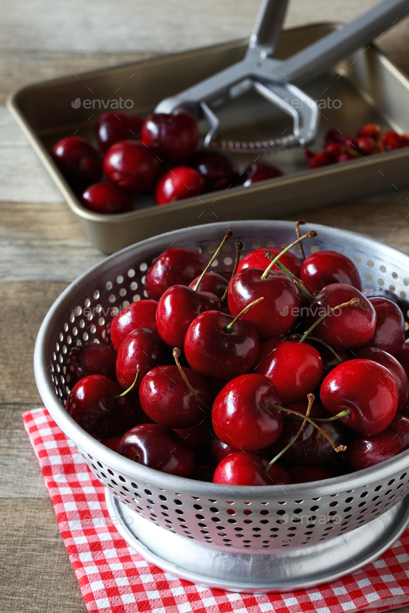 removing pitts from cherries in colander - Stock Photo - Images