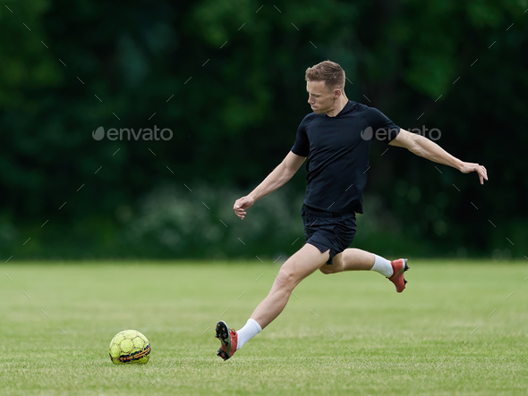 Football player kicking a ball - Stock Photo - Images
