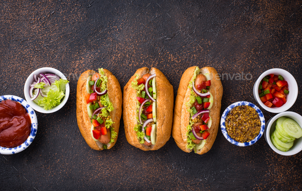 Hot dogs with sausage, sauces and vegetables - Stock Photo - Images