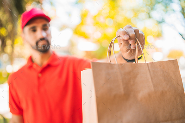 Delivery man carrying packages while making home delivery. - Stock Photo - Images