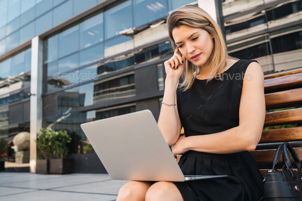 Business woman using her laptop outdoors. - Stock Photo - Images