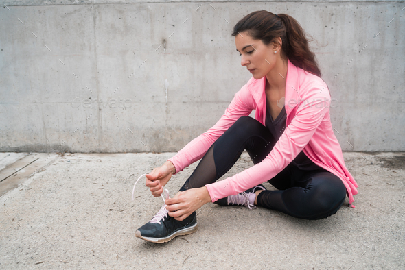 Athletic woman  tying her shoelaces. - Stock Photo - Images