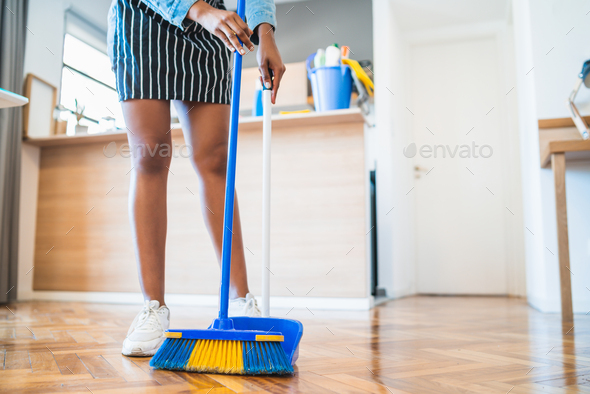 afro woman sweeping floor with broom at home stock photo by megostudio photodune