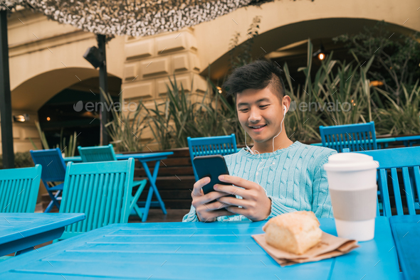 Asian man using his mobile phone. - Stock Photo - Images