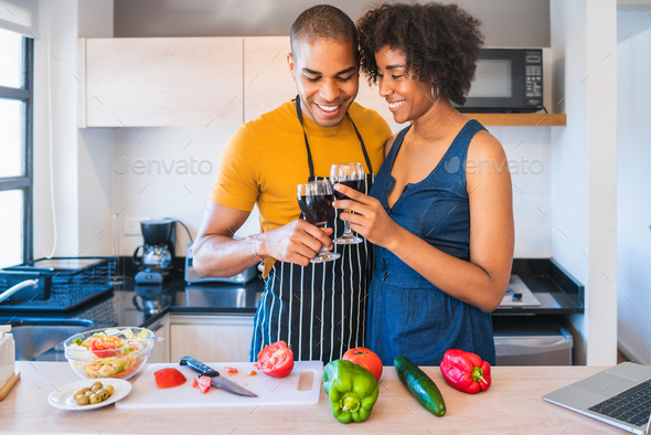 Latin couple cooking together in the kitchen. - Stock Photo - Images