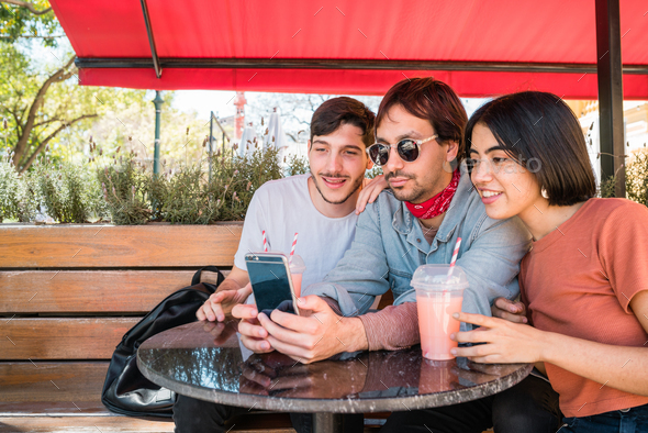Three young friends taking a selfie with phone. - Stock Photo - Images