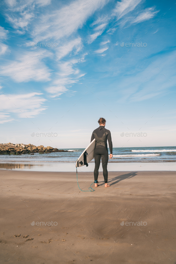 Surfer entering into the water with his surfboard. - Stock Photo - Images