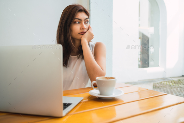 Young woman using laptop at coffee shop. - Stock Photo - Images