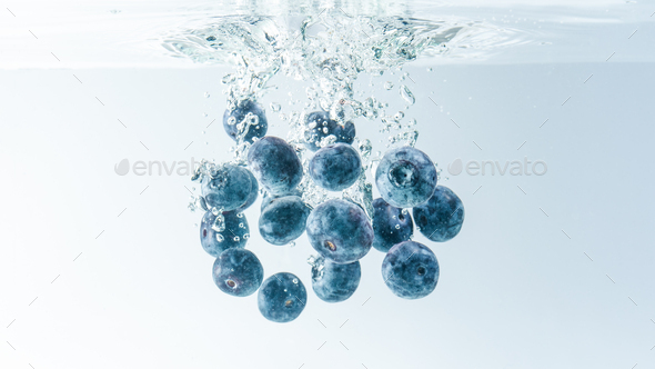 Bunch of blueberries splashing into water surface and sinking. Isolated on white background, splash - Stock Photo - Images