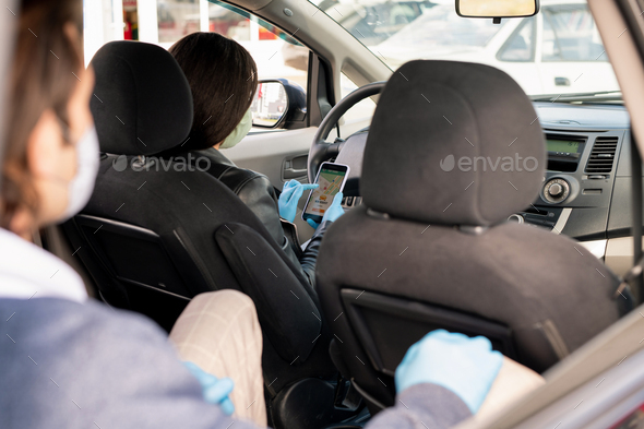 Taxi driver analyzing route to clients destination - Stock Photo - Images