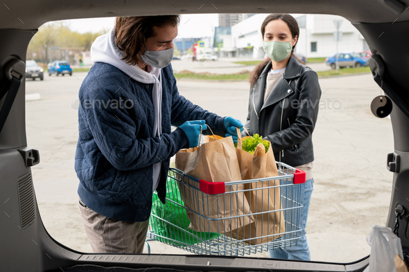 Couple loading bags in trunk - Stock Photo - Images