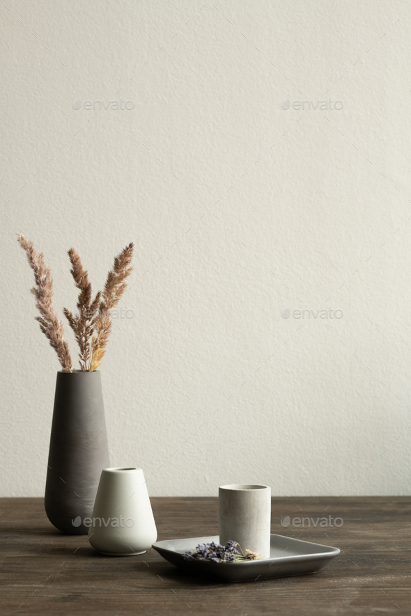 Two white ceramic vases standing on wooden table on background of black one - Stock Photo - Images