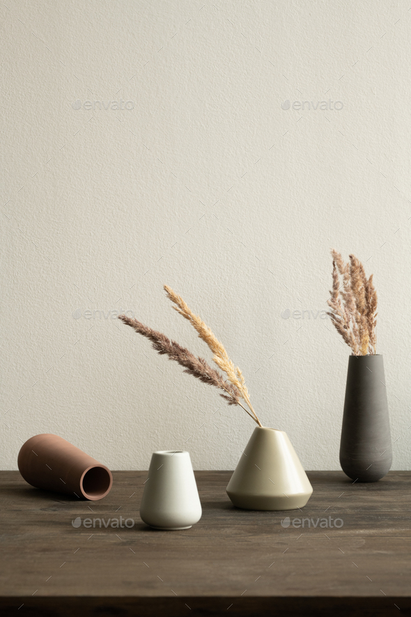 Group of ceramic vases of white and brown colors with dry plants inside - Stock Photo - Images