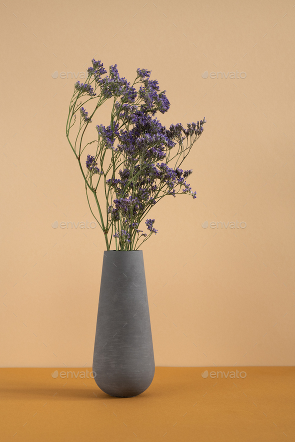 Dried wildflowers in grey clay or ceramic vase standing on table as decoration - Stock Photo - Images