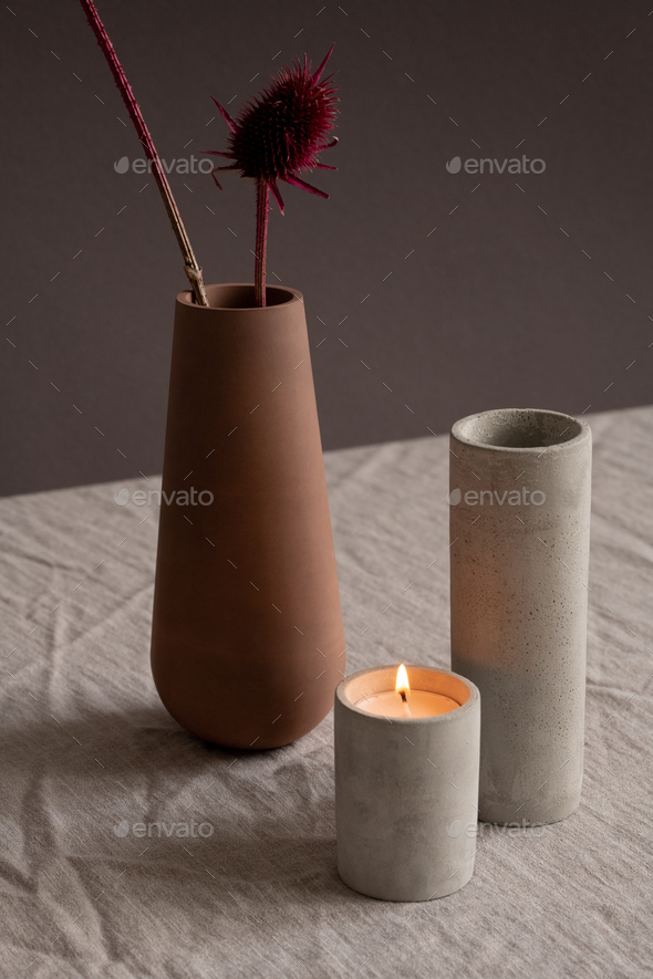 Burning candle, white ceramic vase and brown clay jug with two dry wildflowers - Stock Photo - Images