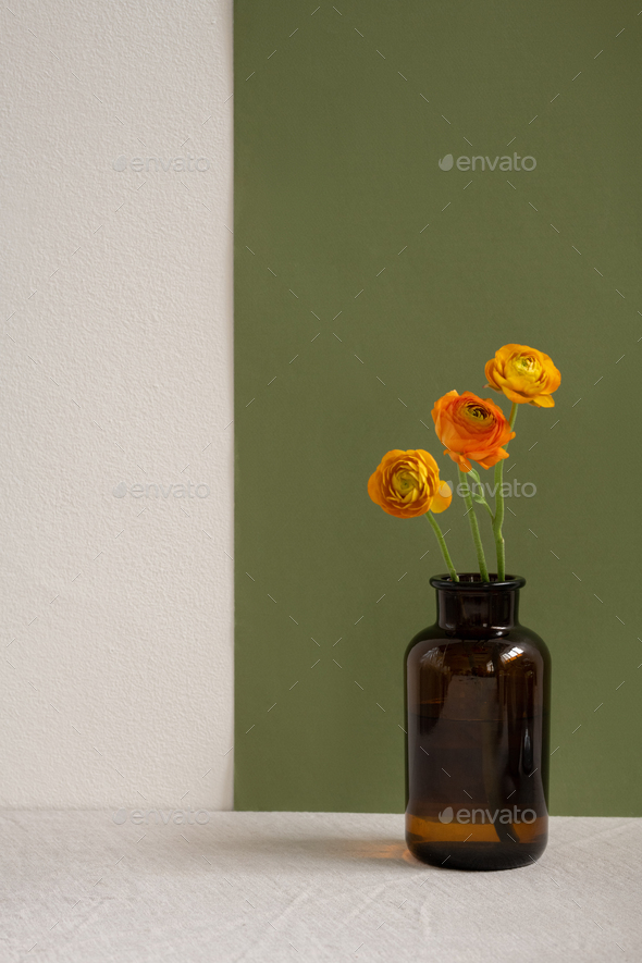 Three yellow dried wildflowers with long green stems standing in dark bottle - Stock Photo - Images