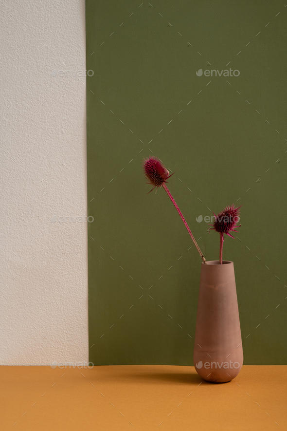 Brown clay handmade vase with two dried wildflowers standing on table - Stock Photo - Images