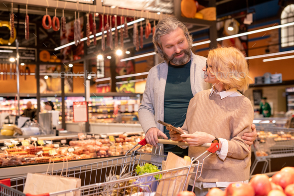 Mature affectionate couple discussing what to buy while shopping in supermarket - Stock Photo - Images