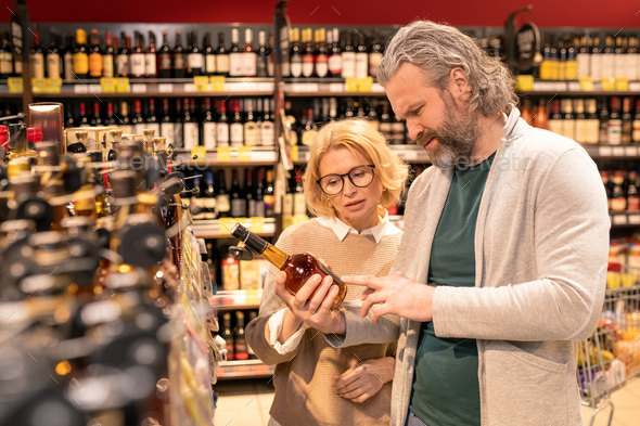 Pretty blond mature woman and her bearded husband reading information on bottle - Stock Photo - Images