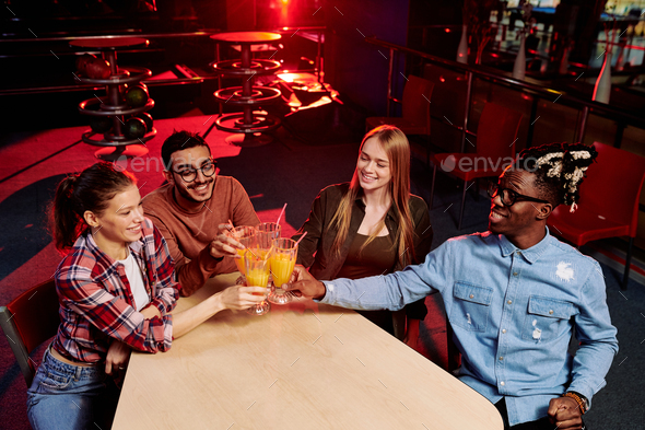 Four multi-ethnic friends in casualwear clinking with glasses of orange juice - Stock Photo - Images