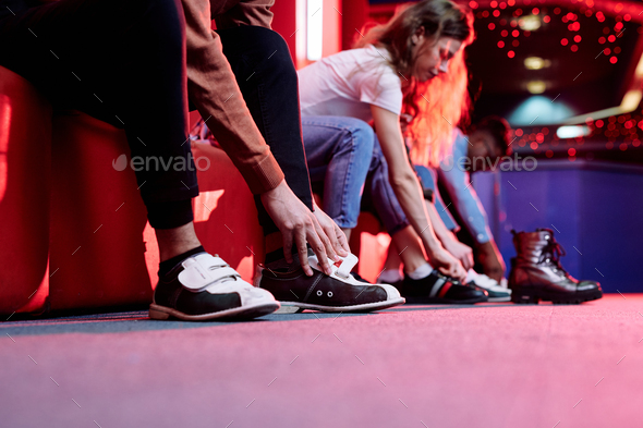 Hands of young man in casualwear putting on shoes for playing bowling - Stock Photo - Images