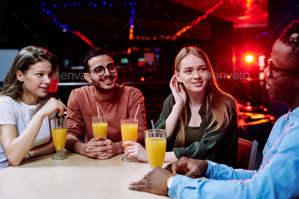 Two girls of Caucasian ethnicity and mixed-race guy listening to African friend - Stock Photo - Images