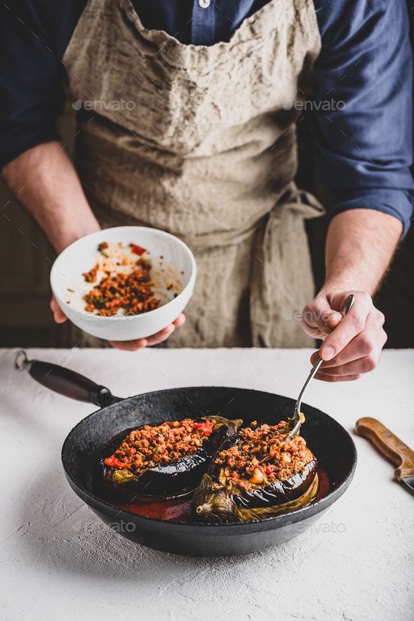 Preparing eggplants stuffed with ground beef, tomatoes and spices - Stock Photo - Images