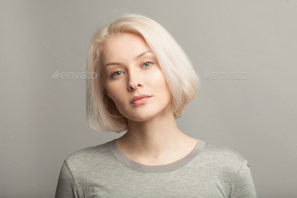 close up portrait of young beautiful blonde woman on gray background - Stock Photo - Images